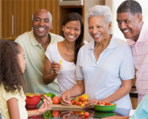 Family gathered in a kitchen, near a counter top full of fresh vegetables.